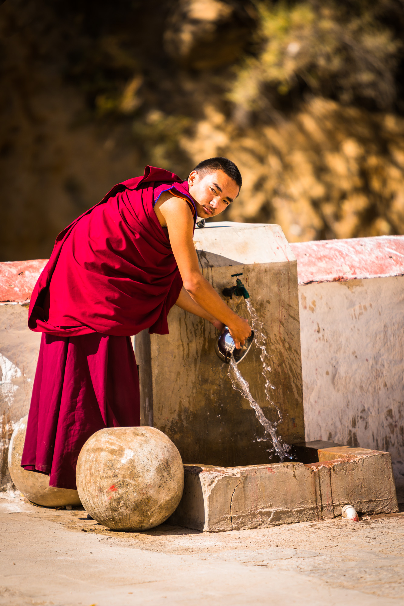 a monk washes his pans, jokhang monastery, lhasa, tibet
